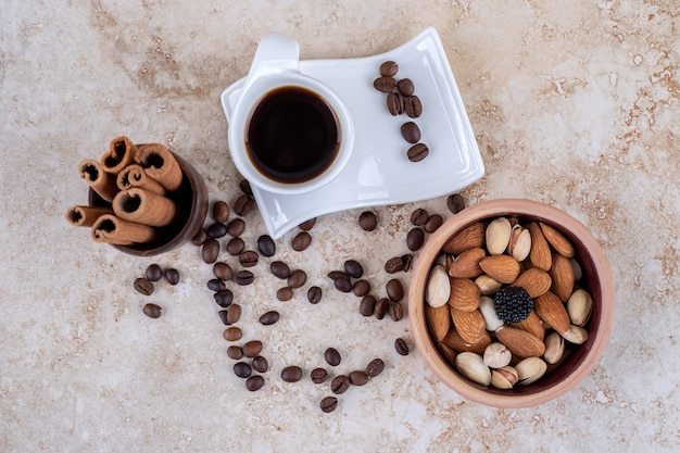 Verspreide koffiebonen, diverse noten, gebundelde kaneelstokjes en een kopje koffie
