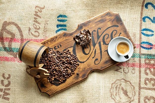 Verspreide koffiebonen, een kopje espresso, stukjes chocolade met noten op een houten bord.