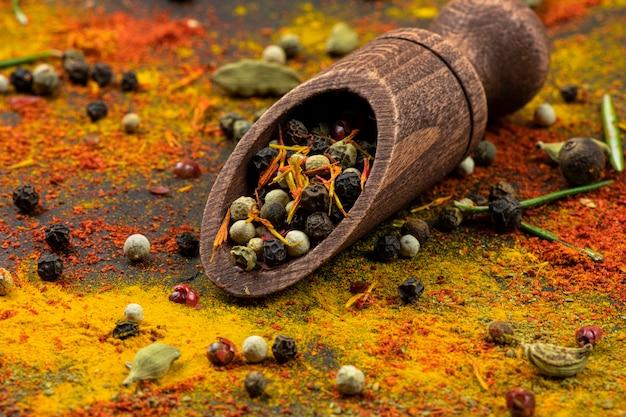 Verspreide kruiden, houten lepel met een mengsel van paprika's op een zwarte achtergrond close-up.