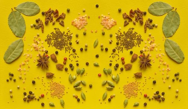 Verspreide kruiden op een gele achtergrond. bovenaanzicht