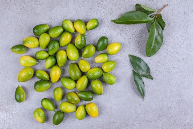 Verspreide kumquats en bladeren op marmeren oppervlak.