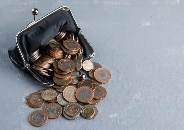 Verspreide munten uit portemonnee op gips tafel.