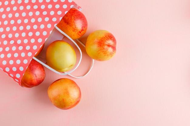 Verspreide nectarines uit een papieren zak op een roze tafel. plat lag.