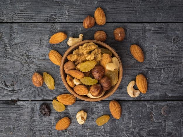 Verspreide noten en gedroogd fruit rond een houten kom op een houten tafel. natuurlijk gezond vegetarisch eten. plat leggen.