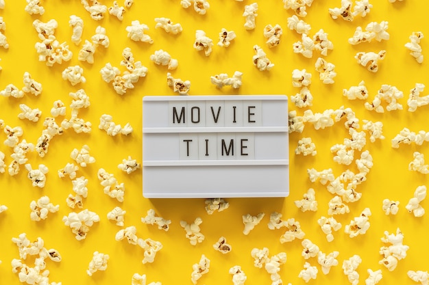 Verspreide popcorn en lightbox-tekst filmtijd op geel papier achtergrond.