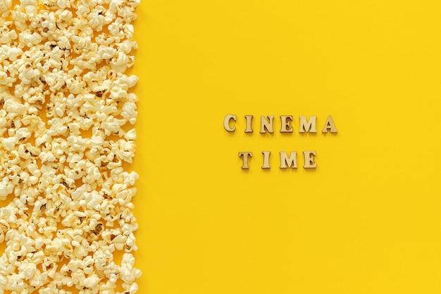 Verspreide popcorn grens linkerrand en bioscooptijd op gele achtergrond.
