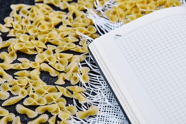 Verspreide rauwe pasta rond notitieboekje op blauwe achtergrond