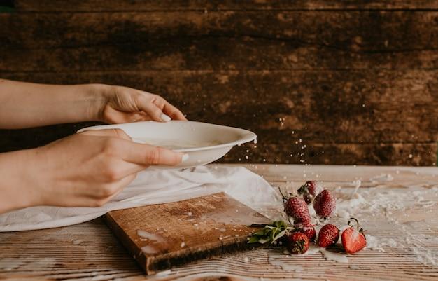 Verspreide sappige verse rode aardbeien op tafel met vintage plank. munt blad. druppels en spatten van gemorste melk.