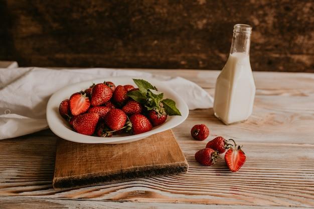 Verspreide sappige verse rode aardbeien op tafel met vintage plank. munt blad.