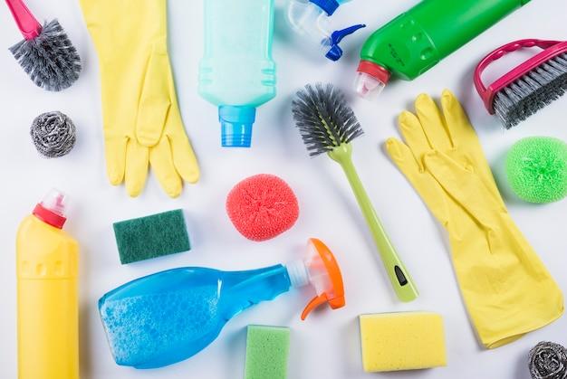 Verspreide schoonmaakproducten op een grijze achtergrond
