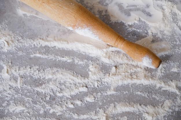 Verspreide tarwemeel en een deegroller op een licht houten tafel. het proces van bakken, koken in de huiskeuken. het concept van verslaving aan koken, koken.