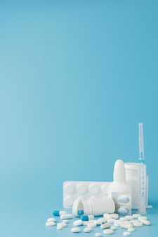 Verspreide verschillende pillen, drugs, sterilisatie, flessen, thermometer, spuit en lege winkelwagen. apotheek winkelen concept
