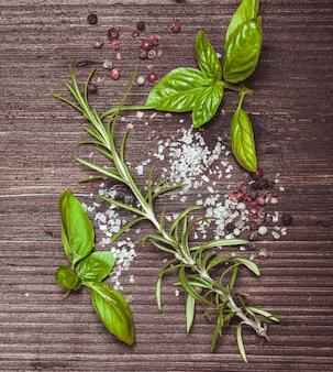Verspreide verse basilicum en rozemarijn, zeezout en droge peperkorrels