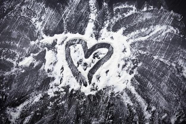 Verspreide witte bloem met geschilderd hart op zwarte ondergrond.