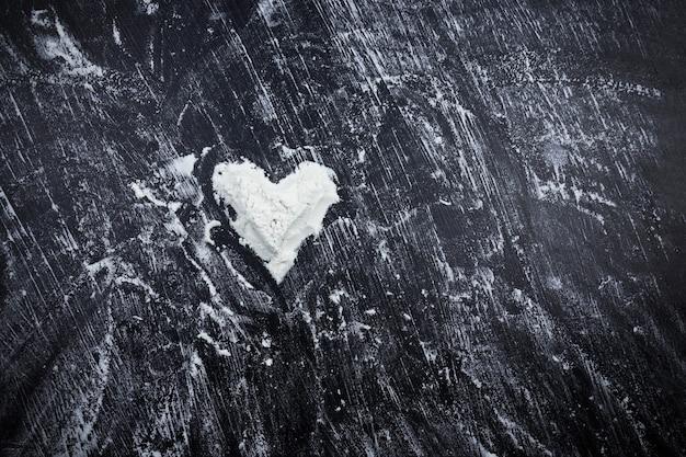 Verspreide witte bloem met hartvorm op zwarte ondergrond.