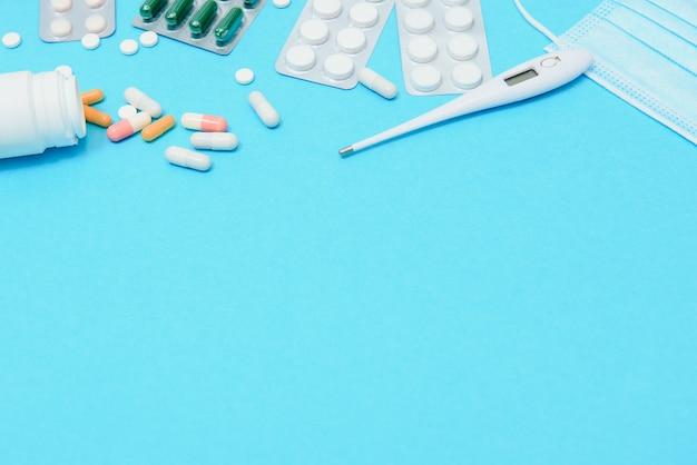 Verspreide witte pillen op blauwe tafel. medische, apotheek en gezondheidszorg concept. blauwe achtergrond witte pillen met een medische statoscope, bovenaanzicht.