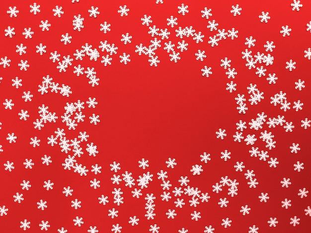 Verspreide witte sneeuwvlokken op rode achtergrond. eenvoudig plat leggen met kopie ruimte.