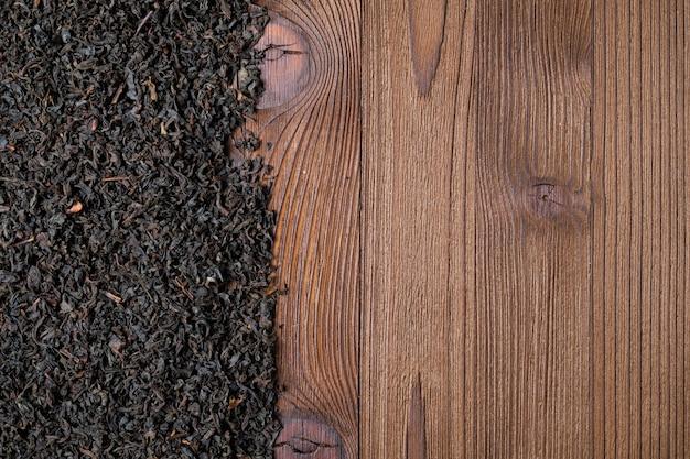 Verspreide zwarte thee op een houten achtergrond met exemplaarruimte.