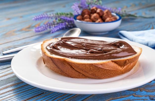 Verspreiding van hazelnootcrème op witbrood, chocolade notenboter op schoollunch toast