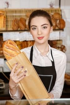Versste brood in de stad. verticaal portret van een jonge bakkersvrouw die vers brood glimlachen houdt