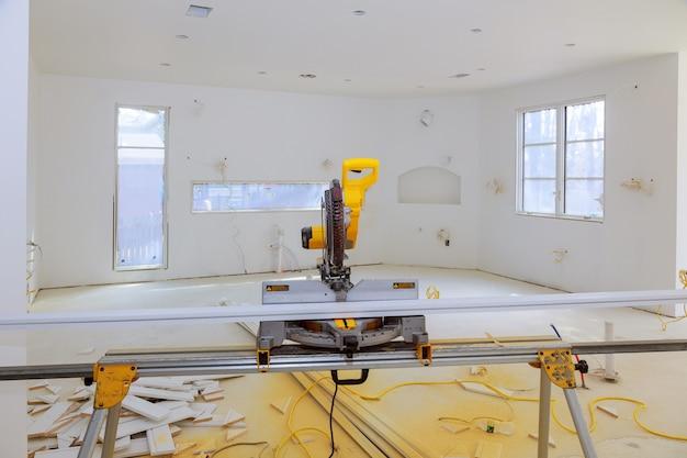 Verstekzaag op een bouwplaats met in aannemer gebruikt een cirkelzaag om te snijden en af te snijden