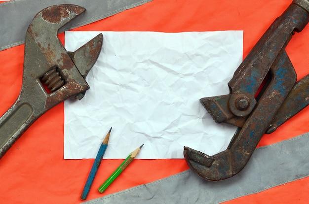 Verstelbare moersleutels en een vel papier met twee potloden