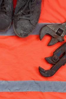 Verstelbare moersleutels en oude laarzen liggen op een oranje signaalarbeidersoverhemd