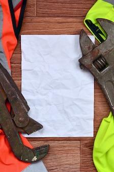 Verstelbare moersleutels en papieren leugens van een oranje en groene signaalbewerkersoverhemden