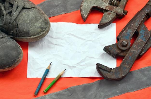 Verstelbare moersleutels met oude laarzen en een vel papier met twee potloden