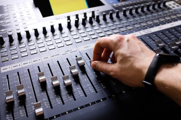 Versterkende apparatuur die de studioknoppen en faders van de audiomixer aanpast. werkplek en uitrusting van de geluidstechnicus. akoestische mixen van muziek