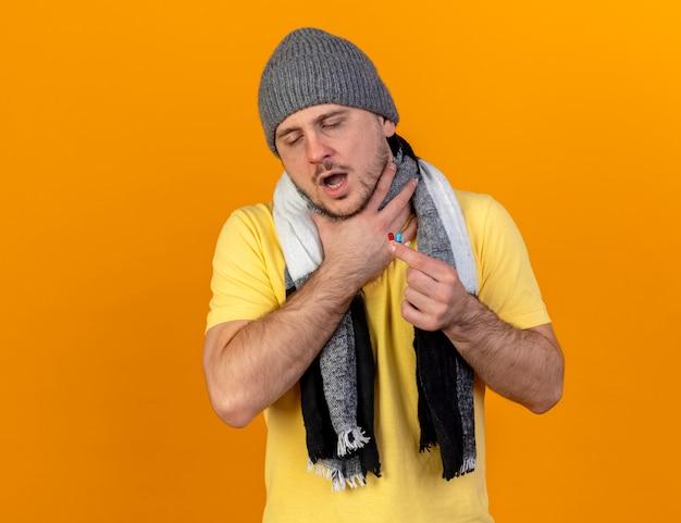 Verstikking jonge blonde zieke slavische man met winter hoed en sjaal houdt nek en medische capsules geïsoleerd op oranje muur met kopie ruimte