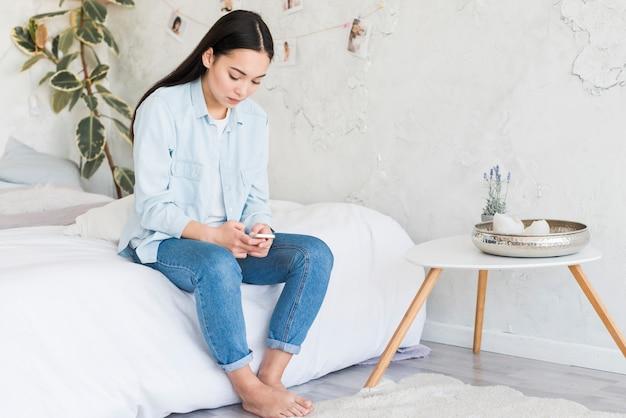 Verstoor jonge vrouwenzitting op bed met mobiele telefoon