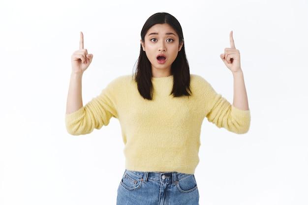 Verstoord en bezorgd schattig aziatisch meisje dat gealarmeerd kijkt en naar boven wijst om je advies of mening te kennen, angstige gedachten te hebben die met het probleem omgaan, hulp vragen bij de keuze, staande witte muur