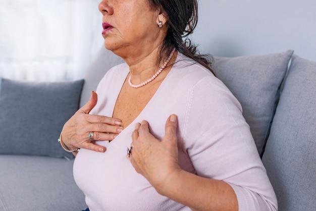 Verstoorde beklemtoonde rijpe midden oude vrouw die pijnpijn voelt wat betreft borst die hartaanval heeft