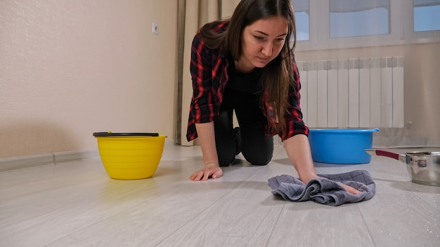 Verstoorde dame in shirt veegt water af dat uit het plafond stroomt na regen met tapijt in de buurt van containers op de vloer in een donkere flat. concept van het overstromen van het appartement en de eigendomsverzekering.