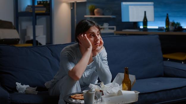 Verstoorde depressieve teleurgestelde vrouw die verloren kijkt op tv en lijdt aan fychotische gedachten die denken aan ...