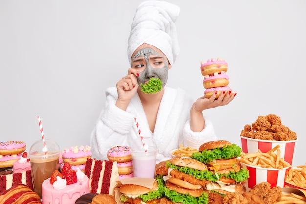 Verstoorde gestresste vrouw die het diëten beu is, heeft een hekel aan groen eten en veegt tranen weg terwijl ze naar smakelijk junkfood kijkt