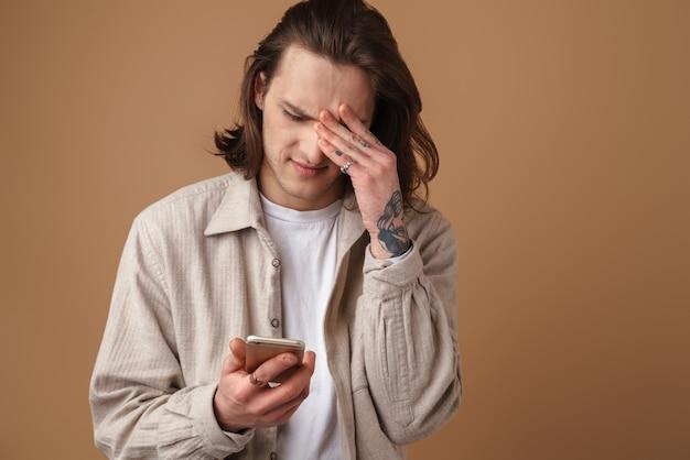 Verstoorde jonge aantrekkelijke man met vrijetijdskleding die geïsoleerd over een beige muur staat en mobiele telefoon vasthoudt