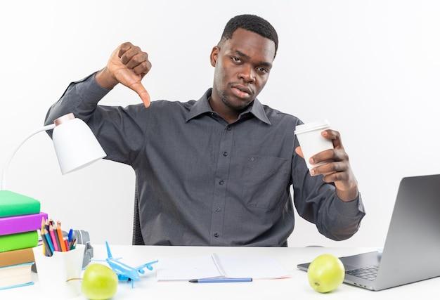 Verstoorde jonge afro-amerikaanse student die aan het bureau zit met schoolhulpmiddelen die een papieren beker vasthouden en naar beneden duimen