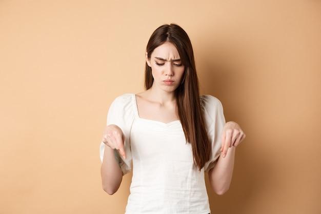 Verstoorde jonge vrouw die fronst en naar beneden kijkt, wijzend op een slechte zaak die verward en ontevreden staat...