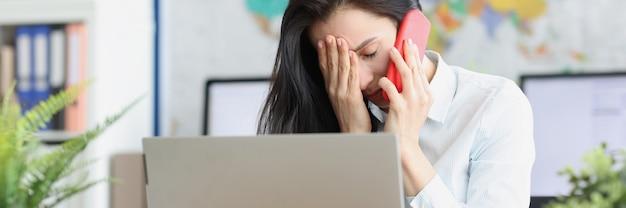 Verstoorde jonge vrouw die op smartphone praat terwijl ze op de werkplek zit