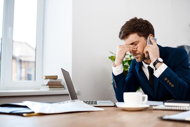 Verstoorde jonge zakenman die op telefoon, bureauachtergrond spreekt.