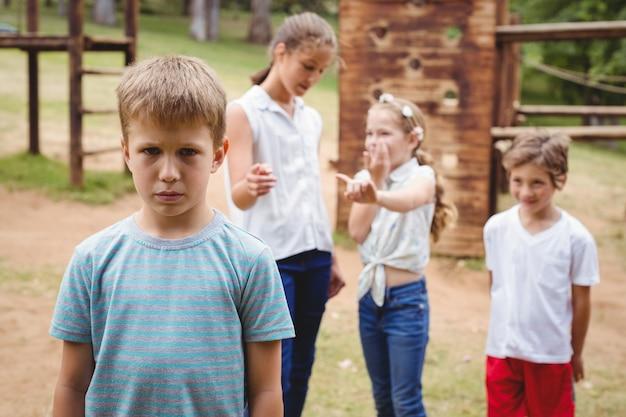 Verstoorde jongen met vrienden die op achtergrond roddelen