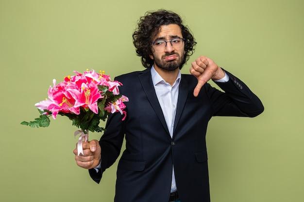 Verstoorde knappe man in pak met een boeket bloemen die er verward en ontevreden uitziet met duimen naar beneden en viert internationale vrouwendag 8 maart staande over groene achtergrond