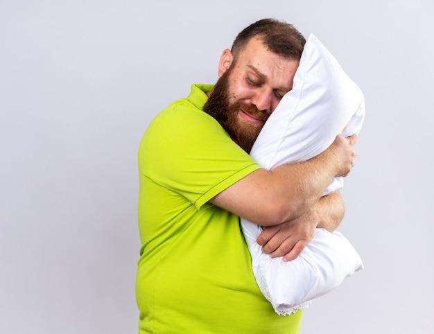 Verstoorde, ongezonde, bebaarde man in geel poloshirt voelt zich ziek en houdt kussen vast en wil slapen terwijl hij over een witte muur staat