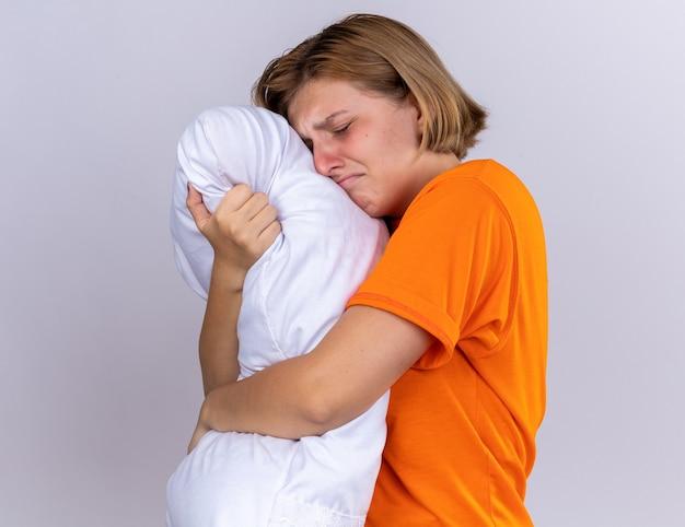 Verstoorde, ongezonde jonge vrouw in oranje t-shirt met kussen die zich ziek voelt en lijdt aan griep die hard staat te huilen over een witte muur