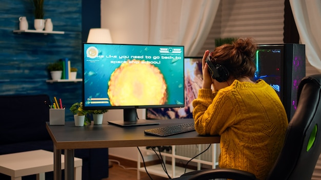 Verstoorde professionele vrouwengamer die een headset draagt en een schietspelronde verliest in de cybersportcompetitie. vermoeide speler die online videogames speelt op een pc met een draadloos netwerk met moderne technologie