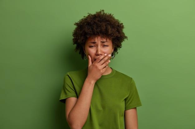 Verstoorde stressvolle vrouw in wanhoop, voelt zich depressief, snikt of huilt luid, kan niet stoppen met huilen, staat voor een lastige situatie, staat bedroefd tegen een levendige groene muur. negatieve emoties concept