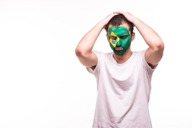 Verstoorde verliezersfan steun van het nationale team van brazilië met geschilderd gezicht geïsoleerd op een witte achtergrond