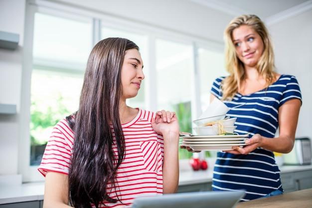 Verstoorde vrouw die vuile schotels tonen aan vriend in keuken
